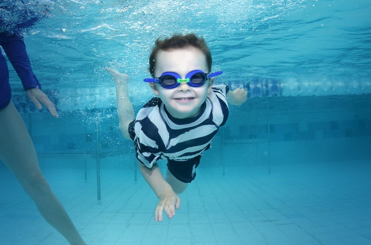 Child swimming underwater wearing goggles